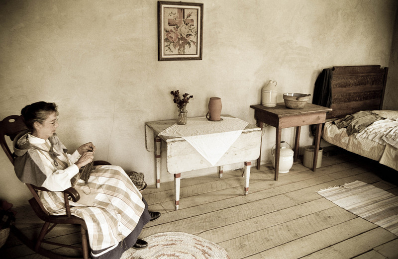 An interpreter knits in the one-room 1900 Kruza farmhouse while waiting for vistors.
