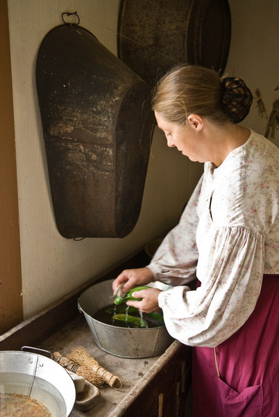An interpreter in the Schulz farm washes cucumbers she will serve for dinner.