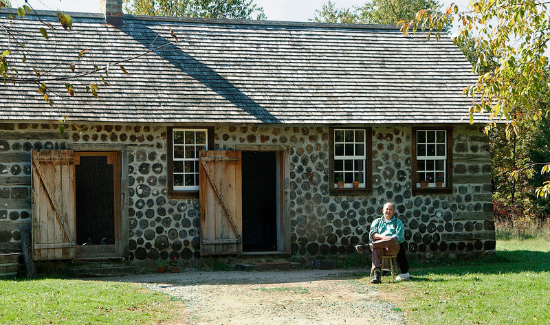 "An interpreter awaits visitors at the 1900 Kruza  house.  This house was built by a Polish farmer for his aging in-laws.  Note the ""stovewood"" construction of the walls.  The section on the left housed chickens while the residents lived in the right side of the house."