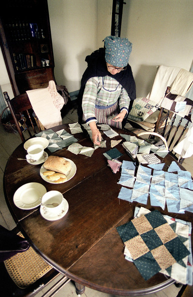 An interpreter sorts squares of fabric that will be used to make a quilt at the Koepsell farmhouse.