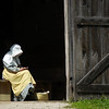 An interpreter sits at the entrance to the Grube barn on the Schullz farm.