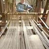 An interpreter weaves on the loom at the Schulz (German) farm.