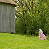 An interpreter walks past the Grube barn on the Schulz farm on a beautiful spring day.