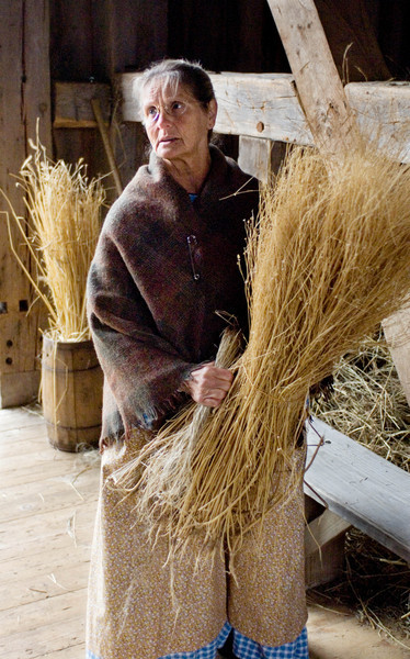 An interpreter holds a sheave of flax prior to carding it.