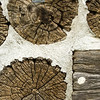 """Detail of the """"stovewood"""" construction used for the 1900 Kruza (Polish) house.  Marker tags like those on upper log were used when the house was disassembled for transport to Old World.  Each log was numbered so it could be reassembled in the proper order."""