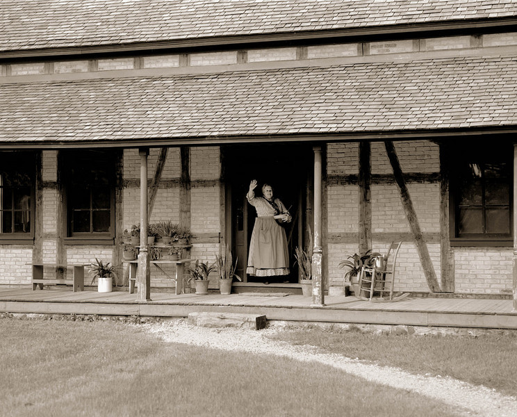 An interpreter waves to visitors from the entrance to the 1880 Koepsell (German) farmhouse.