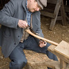 "An interpreter at the Koepsell farm uses a ""schnitzelbank"" to hold an ax handle he is carving with a drawknife."