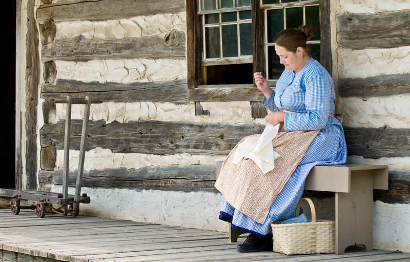 An interpreter relaxes while sewing on the front porch of the Schottler farmhouse.  The device on the left is a stove dolly that was used to move the cast iron cookstove from the farmhouse interior kitchen to the summer kitchen each spring, then back again in the fall.