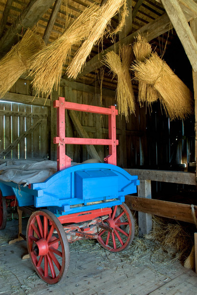 Hay wagon and sheaves of straw hanging in the Grube barn on the Schulz farm.  The straw was used for the thatched roof of the barn.