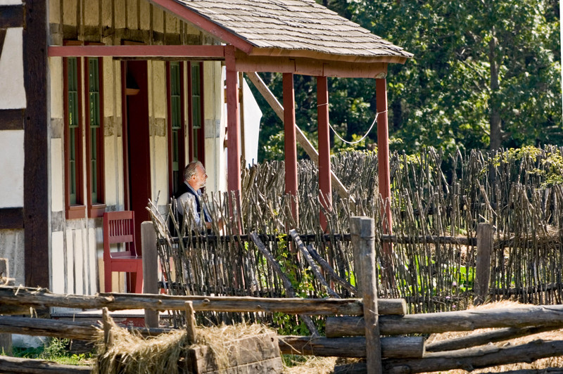 An interpreter relaxes on the front porch of the 1860 Schulz farmhouse.  Note the twig fence that protects the garden area.  Fences were needed to keep wild animals from damaging the plants  and twigs were plentiful in the New World.