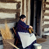 An interpreter weaves baskets on the front porch of the 1875 Schottler farmhouse.