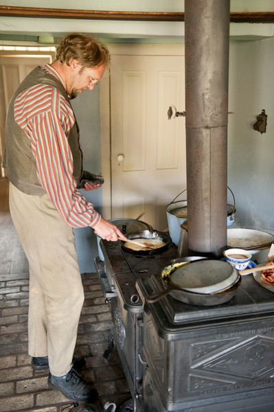 An interpreter in the Koepsell farmhouse kitchen prepares dinner on a cast iron wood cookstove.