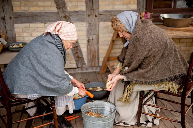 The cook's helpers prepare vegetables on the back porch of the 1880 Koepsell farm.