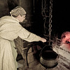 "An interpreter tends a fire in the oven in the ""black kitchen"" of the 1860 Schulz farmhouse.  The black kitchen was basically a large chimney in the center of the house.  Meat was smoked by hanging it on racks in the chimney.  Bread was baked by first building a fire in the oven.  After the bricks lining the inside of the oven were sufficiently hot, the coals were removed by dragging them into the pit below the pot seen here.  Many loaves of bread were then placed in the hot oven to bake. Black kitchens fell out of use after a number of years because of the  fire hazard they presented  --- especially to women wearing long skirts."