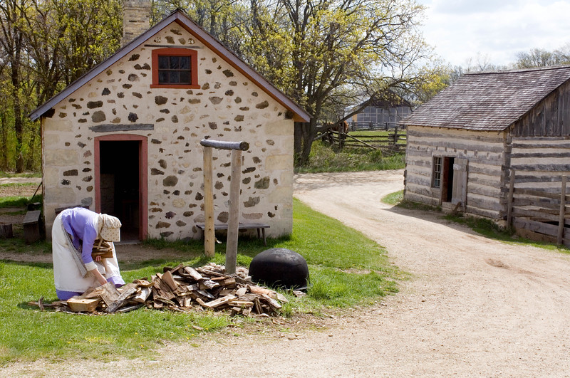 An interpreter hauls firewood to the wood stove in the summer kitchen located behind her on the 1875 Schottler (German) farm.
