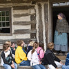 An interpreter greets young students on a school field trip before inviting them in and showing them the 1875 Schottler farmhouse.