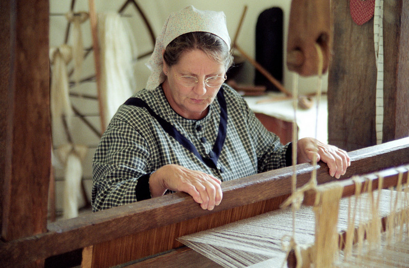 An interpreter weaves with the large loom in the 1860 Schulz farmhouse.