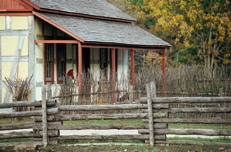An interpreter sits on the front porch of the Schulz farmhouse.  Note the twig fence that protects the garden area.  Fences kept wild animals from damaging the plants,  and twigs were plentiful in the New World.