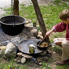An interpreter cooks dinner in the firepit below the tripod mounted kettle at the 1845 Fossebrekke cabin in the Norwegian area.