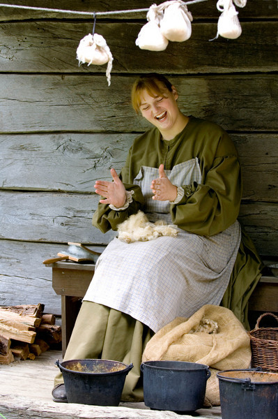 An interpreter cleans wool on the front porch of the 1865 Kvaale farmhouse.'
