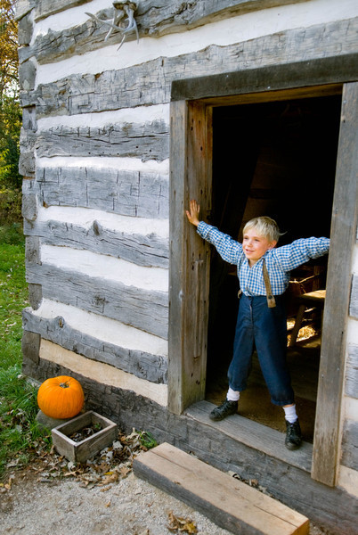A young visitor stands guard at the entrance to the Fossebrekke cabin.