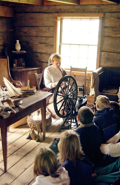 An interpreter demonstrates a spinning wheel to schoolchildren in the 1865 Kvaale farm.