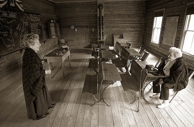 An interpreter chats with a visitor in the 1906 Raspberry one room school house in the Norwegian area.