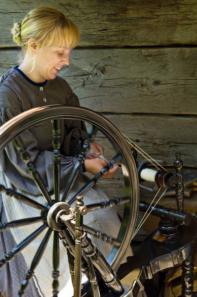 An interpreter moved her spinning wheel out onto the front porch of the Kvaale farmhouse to cool off on a warm day.