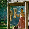 An interpreter inspects yarn hung up to dry on the front porch of the 1865 Kvaale farmhouse.