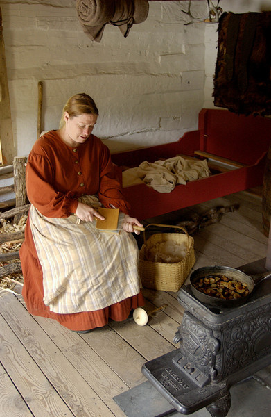 An interpreter cards wool while she cooks dinner in the small 1845  Fossebrekke cabin in the Norwegian area.  Note the skins hanging in the background.  Knud Fossebrekke helped support himself by trapping and well as farming.