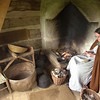 A small outbuilding at the 1865 Kvaale farm, complete with fireplace,  is the site of this interpreter cleaning wool.