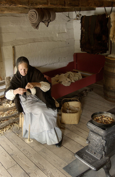 An interpreter uses a drop spindle to spin wool while she cooks dinner in the small 1845  Fossebrekke cabin in the Norwegian area.  Note the skins hanging in the background.  Knud Fossebrekke helped support himself by trapping as well as farming.