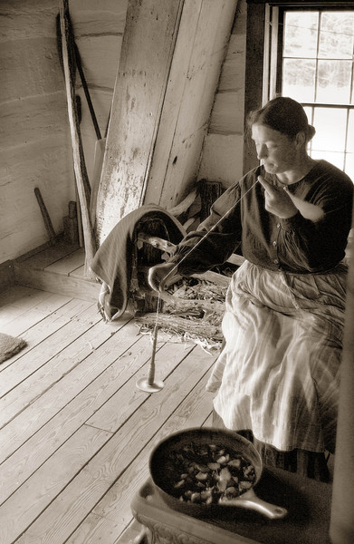 An interpreter uses a drop spindle to spin wool while she cooks dinner in the small 1845  Fossebrekke cabin in the Norwegian area.  Note the steep stairway in the upper left and also the small pigpen behind the interpreter.  Knud Fossebrekke brought his young pigs into the cabin to protect them from wild animals.