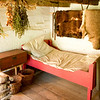 Bed in the 1845 Fossebrekke cabin.  Note the hides on the wall behind the bed.  Knut Fossebrekke was a trapper as well as a farmer.  Also note the small pig pen in the lower left corner.  Fossebrekke used this to keep his young pigs safe warm in the winter and safe from predators.
