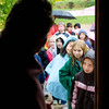 A school group lines up and awaits entry into the Raspberry schoolhouse on a rainy day.