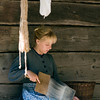 An interpreter cards wool on the front porch of the 1865 Kvaale farmhouse.