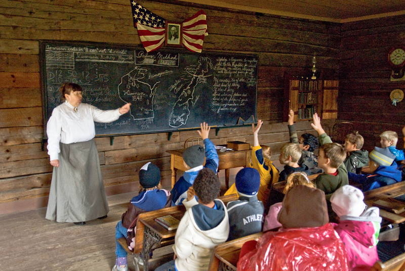 An interpreter quizzes students on Wisconsin history in the 1906 Raspberry school in the Norwegian area.  These fourth grade students on a field trip to Old World have been studying Wisconsin history as part of their school curriculum.