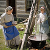 Interpreters do their laundry in the giant tripod mounted kettle outside the 1845 Fossebrekke cabin in the Norwegian area.  This kettle was also used by the Knut Fossebrekke for cooking.