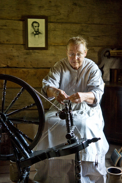 An interpreter spins in the 1865 Norwegian farmhouse.  Note the picture of Lincoln on the wall behind her.