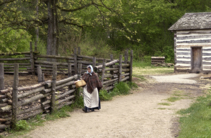 An interpreter walks along the pig sty at the 1845 Fossebrekke Norwegian farm.