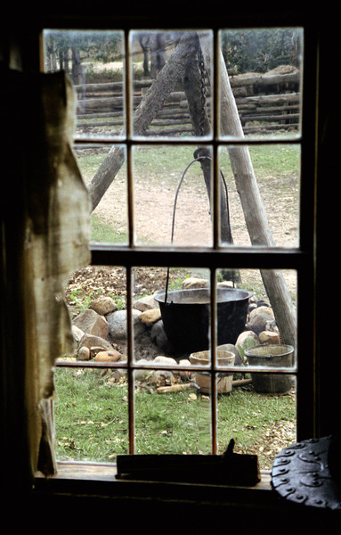 A tripod mounted kettle as seen through a window in the 1845 Fossebrekke cabin. The Fossebrekke cabin was very small and cramped so much of the cooking was done outside in this kettle over an open firepit.