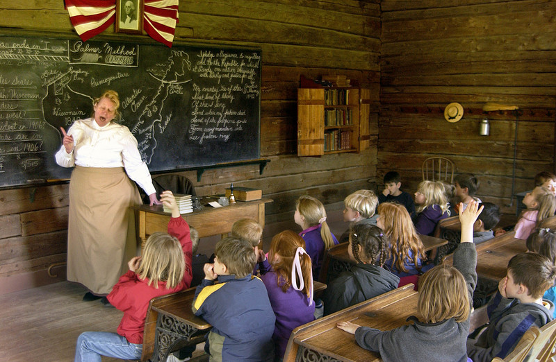 Modern schoolchildren on a field trip visit the one room Raspberry Norwegian school.  An interpreter acting as teacher lays down the law to them and tells them about the difficult life children had in 1906.