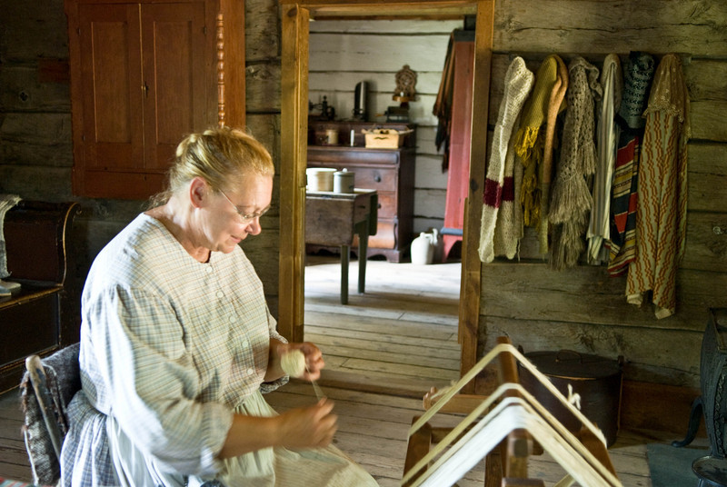 An interpreter winds yarn in the 1865 Norwegian farmhouse.