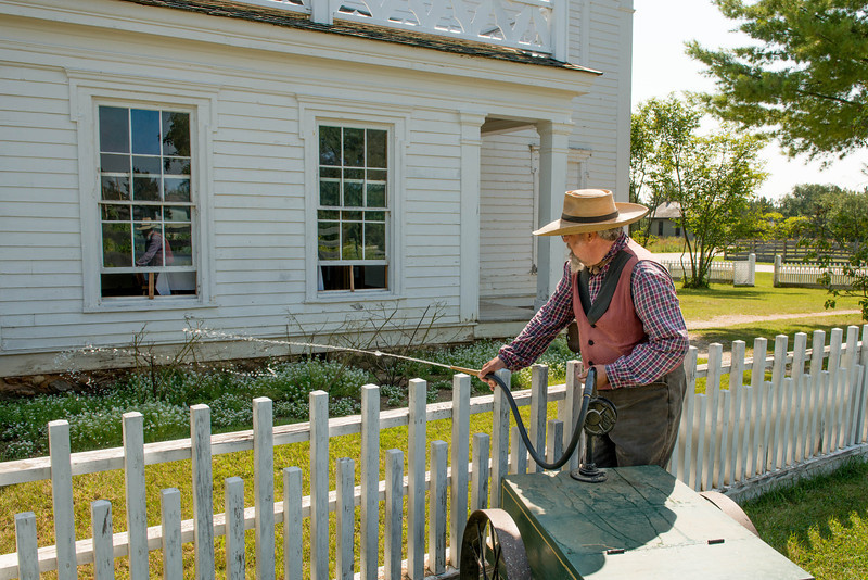 "A gardener uses a Civil War era ""garden machine"" to water plants at Sanford House in Crossroads Village."