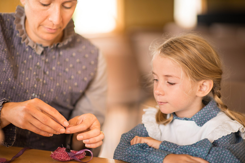 A young visitor makes a pin keeper with help from her mother.