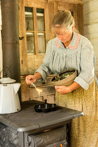 An interpreter makes ebelskivers in the kitchen of the Pedersen Danish farmhouse.