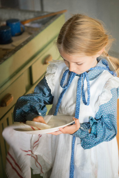 A young visitor helps her mother by drying dishes.