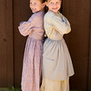 21st century children dressed in 19th century clothes ready to be photographed.