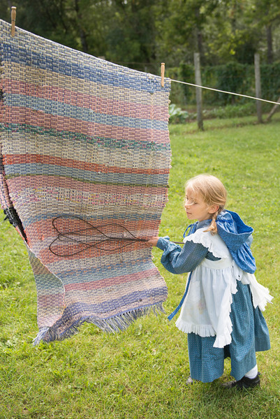 A young visitor uses a carpet beater as one of her spring cleaning chores.