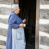 An interpreter stands at the door of the Fossebrekke farmhouse.